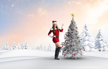 Composite image of sexy santa girl pointing