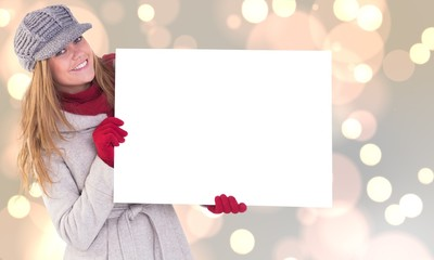 Composite image of happy blonde in winter clothes showing card