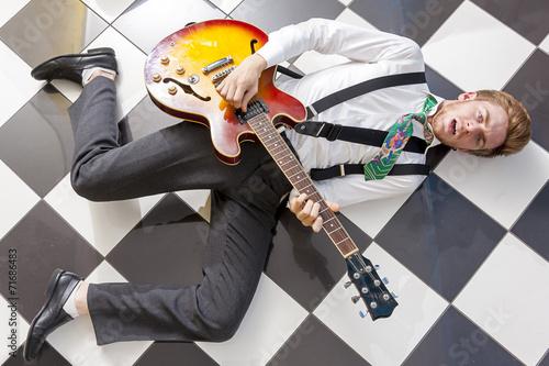 Leinwanddruck Bild fifties style - young guitarist playing lying on the floor