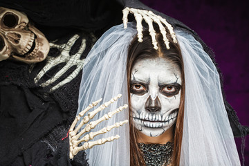 Young woman a bride in a veil day of the dead mask skull face ar