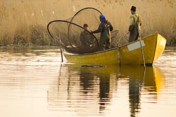 rybacy stawiający sieci