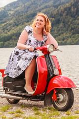 Rothaarige Schönheit mit Übergewicht auf einem roten Motorroller