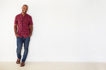 Portrait Of Casually Dressed Man Leaning Against White Wall