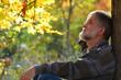 Leinwanddruck Bild - Mann sitzt am Baum