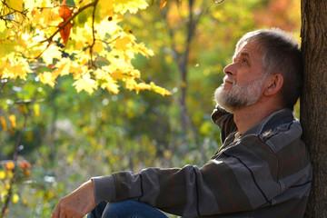 Mann sitzt am Baum
