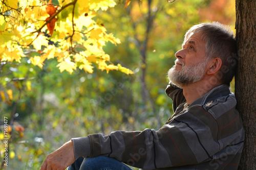 Leinwanddruck Bild Mann sitzt am Baum