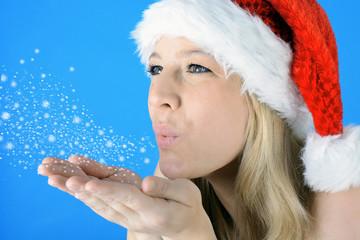 Frau zu Weihnachten pustet Schnee