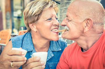 Happy playful senior couple in love driniing cup of coffee