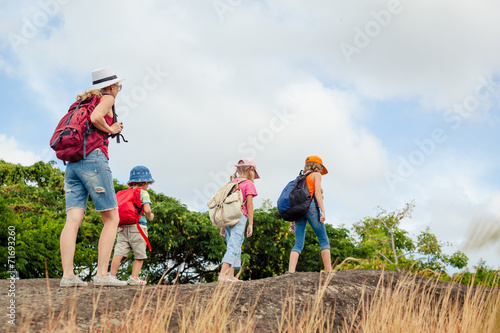 three little kids and mother in the mountains - 71693260