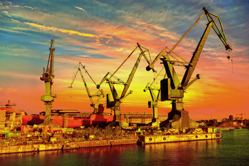 Big industrial cranes on a sunset sky background.