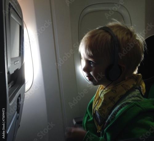 canvas print picture Kind schaut fernsehen im Flugzeug