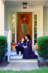 Happy smiling mother and son on a fall decorated porch