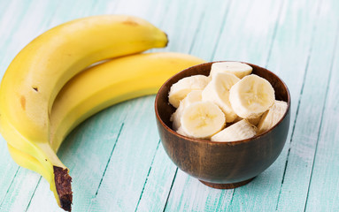 Sliced banana in bowl on  wooden background. Selective focus.