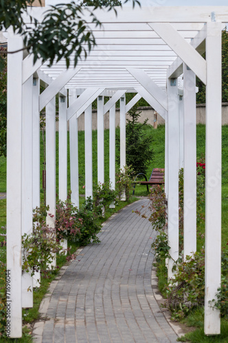 wooden arch tunnel at the entrance of a garden - 71696044