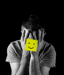 young man in depression and stress with smiley face post it note