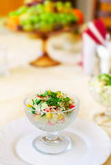 Vase with vegetable salad on a table