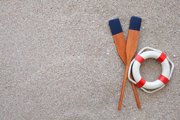 paddles and life buoy lying on a sand
