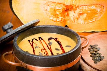 Kürbissuppe mit Kernen, Öl, auf Holz Boden