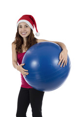 Christmas fit woman holding a blue pilates ball