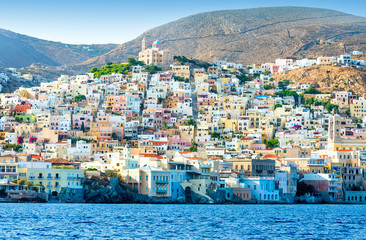 Greek island with colorful houses and yachts.