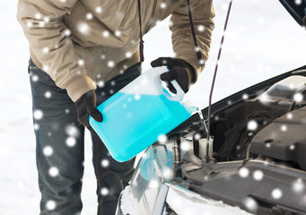 closeup of man pouring antifreeze into car