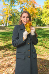 Smiling Young Woman in Gray Coat Holding Leaves