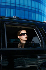 Serious Woman in Shades Inside Expensive Car
