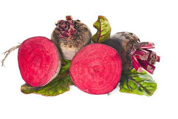 Raw beets with leaves on a white background.