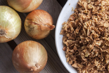 Few onions and a bowl  with dry onion flakes