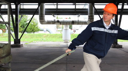 worker pulls heavy metal cart under gas cooler unit, close-up