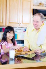 Elderly man sharing cookies with granddaughter