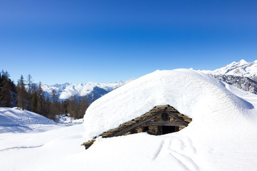 Casa innevata in montagna
