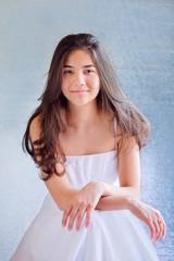 Beautiful biracial teen girl in white dress, sitting arms crosse