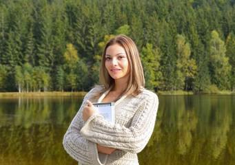 Beautiful young woman relaxing near a lake