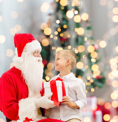 smiling little boy with santa claus and gifts
