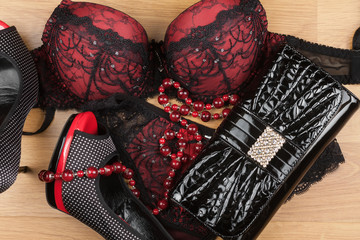 Lingerie,beads, shoes and bag  lying on the laminate