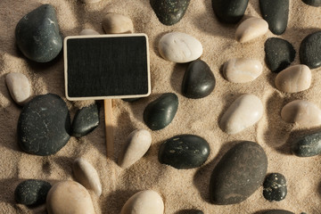Close-up of stones and sign sticking out of the sand in the sunl