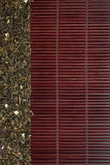 Dried  green tea  on a dark  bamboo mat