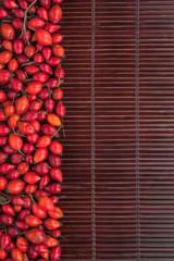 Rosehip on a dark  bamboo mat