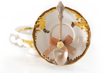 Silver teaspoon with a bow on golden background cup saucer.