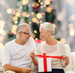 happy senior couple with gift box at home