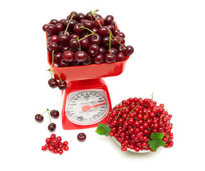 red currant berries and cherries and kitchen scales on a white