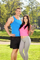Young couple in sportswear posing in park