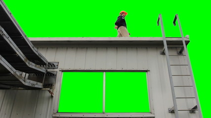 worker goes at roof of house and climbs down, green screen