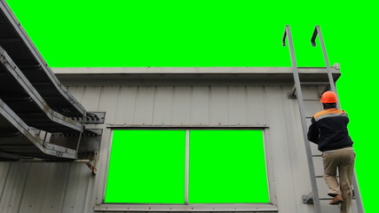 worker climbs up to house and goes out on roof, green screen