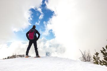 Uomo osserva cielo con nuvole in montagna d'inverno con ciaspole