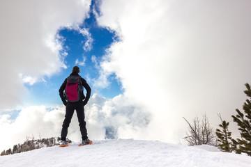 Persona osserva cielo in montagna d'inverno con ciaspole