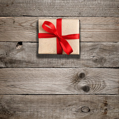 Gift box with red bow on wooden background