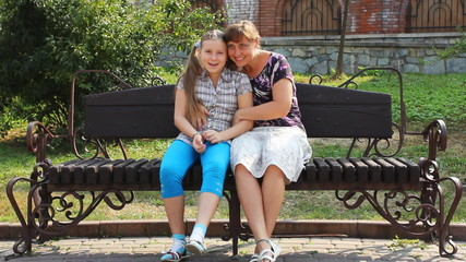 happy mother hugs her daughter sitting on beautiful bench