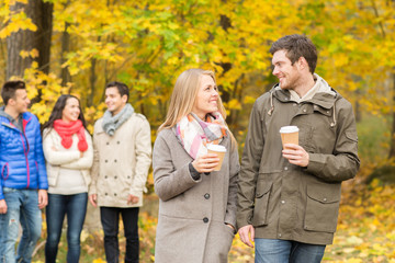 group of smiling friend with coffee cups in park